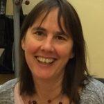 Jennifer Moreau. Brown mittlelong ahir, grey jumper smiling happily.