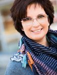 Esther Horvath Tothne, black short hair, glasses, striped scarf and light blue pullover, smiling.