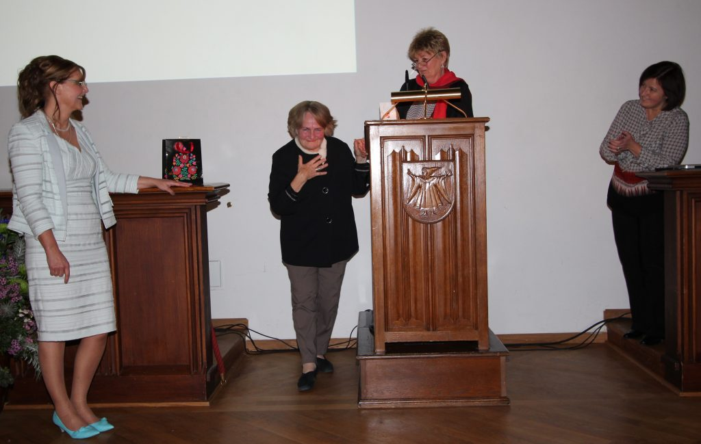 Old picture with old colors whowing Helga Keil next to podium and 3 people looking at her, clapping hands, smiling. Helga Keil bows.