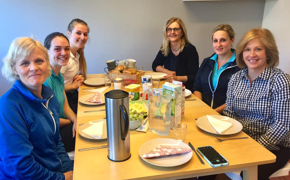 Group picture of 6 sitting at table in Norway with PTO Norge having a meal.