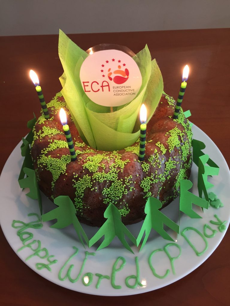Marble cake on white plate with green decoration, 4 green candles and ECA logo on top for WCPD.