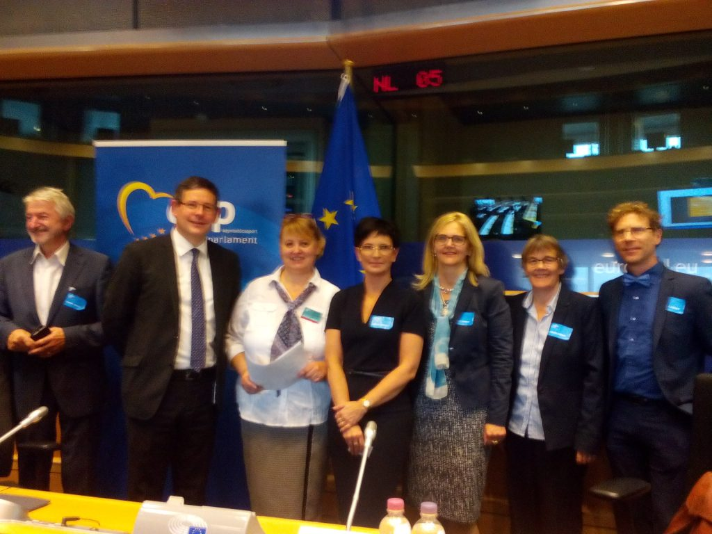 Eu Parliament. A group of 7 people standing up with EU flag at the back. Amongst them ECA, Mr. von Quadt and others.