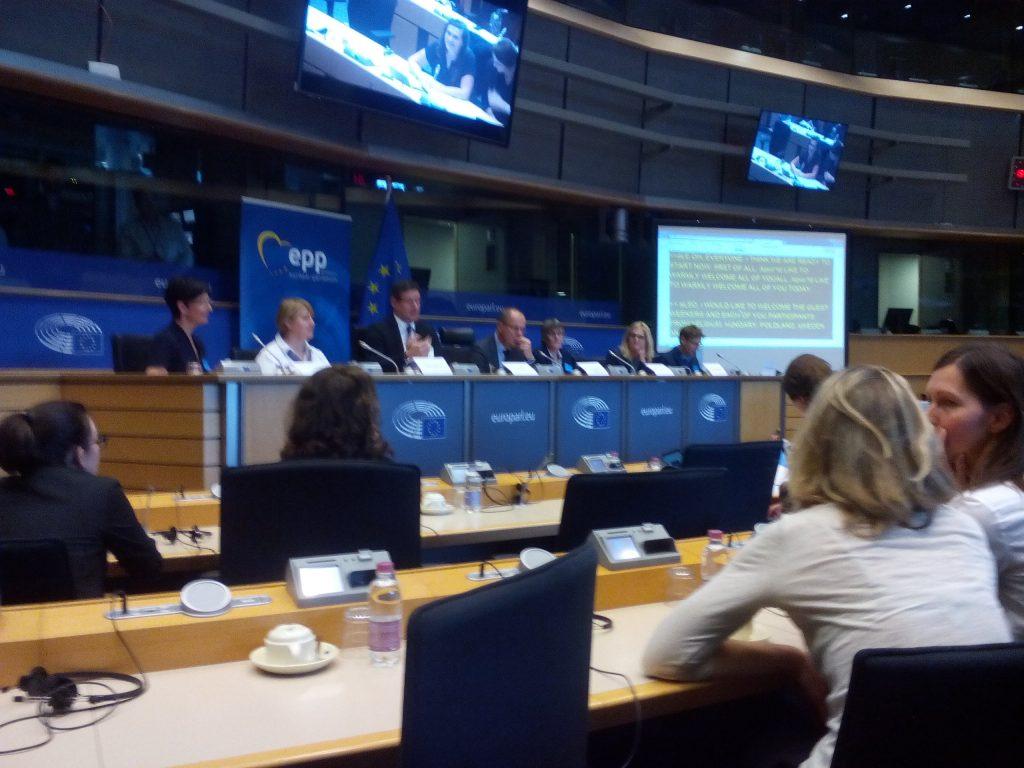 Podium at Eu parliament showing ECA members and EU flag.