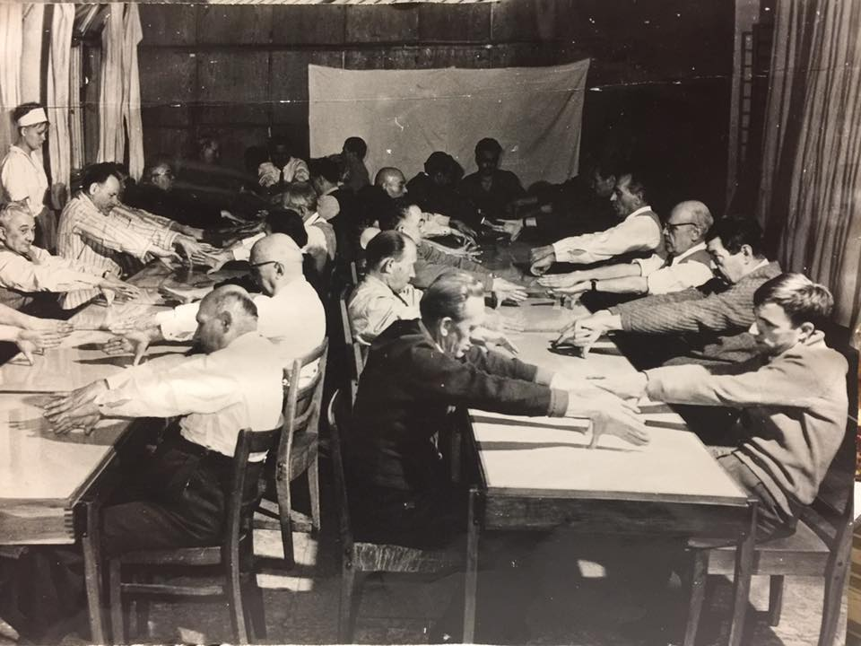 Black and white picture.Two tables, two groups of adults. One teacher on the side. The adults stretch out their hands towards the person opposite of their table.